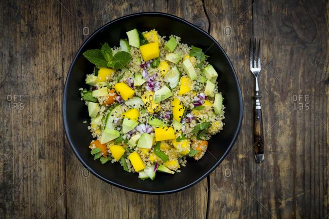 Bowl of quinoa salad with mango- avocado- tomatoes- cucumber- herbs and black sesame