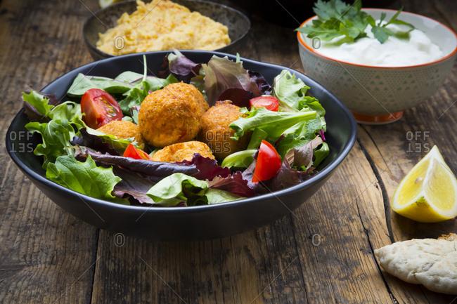 Bowl of mixed salad- tomatoes- sweet patato Falafel and Hummus- yoghurt sauce and flat bread