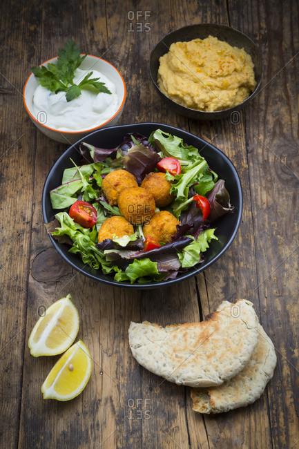Bowls of mixed salad- tomatoes- sweet patato Falafel and Hummus- yoghurt sauce and flat bread