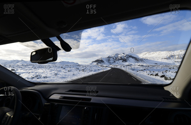 Iceland- road and snow-capped mountain seen from inside car