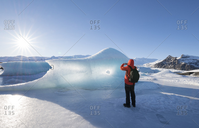 Iceland- tourist taking cell phone picture of glacial ice