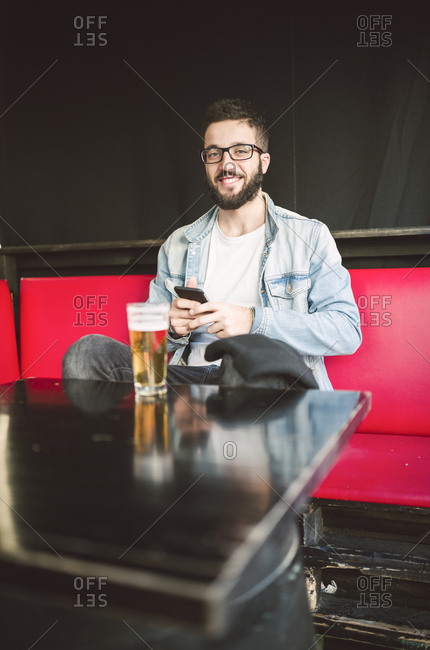 Portrait of smiling young man sitting in a pub