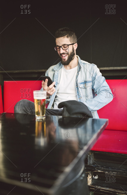 Smiling young man sitting in a pub reading messages on smartphone