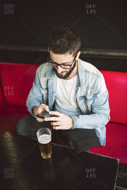 Young man sitting in a pub text messaging