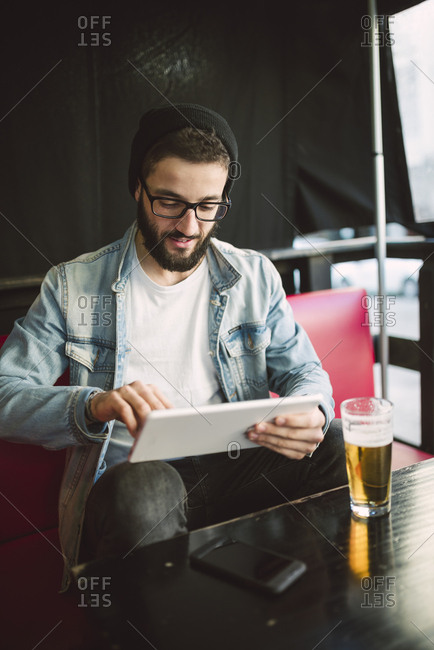 Young man sitting in a pub using tablet
