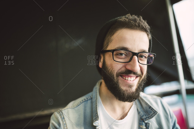Portrait of bearded young man wearing glasses and hat