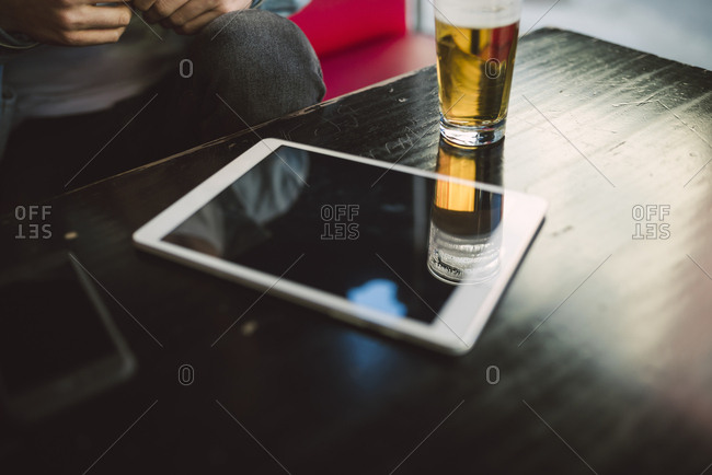Tablet and glass of beer on table