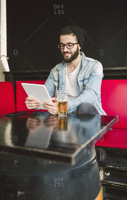 Smiling young man sitting in a pub using tablet