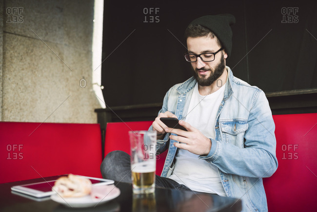 Young man sitting in a pub checking messages