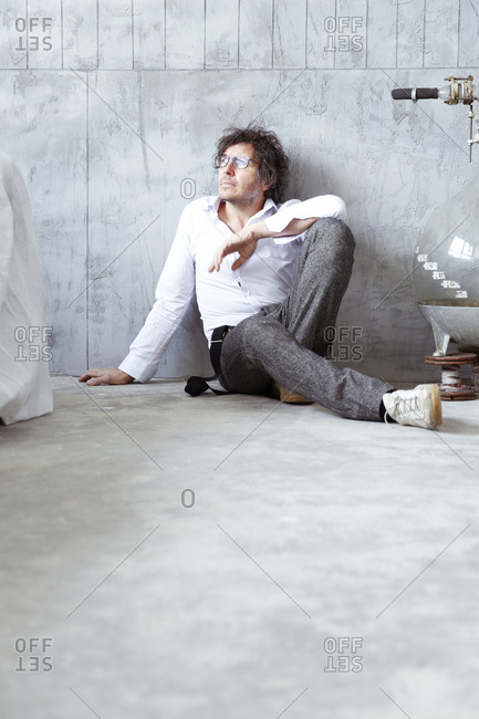 Architect sitting on the floor at construction site
