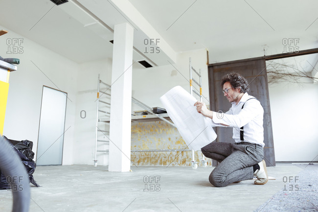 Architect with construction plan at construction site