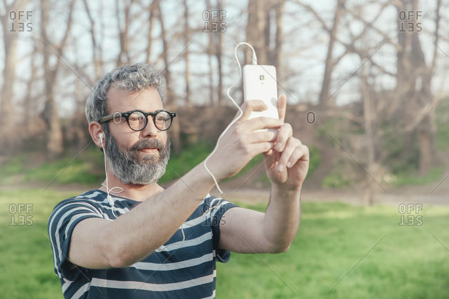Bearded man taking selfie with smartphone