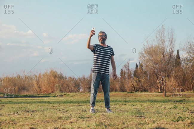 Man standing on a meadow taking photo with smartphone