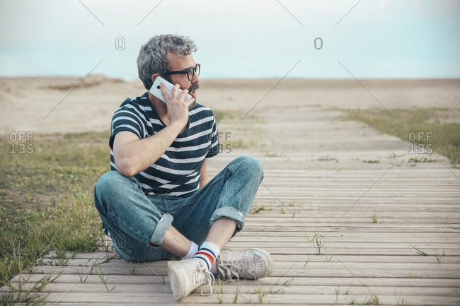 Man on the phone sitting on boardwalk looking at distance