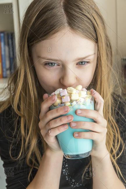 Girl drinking glass of unicorn milk