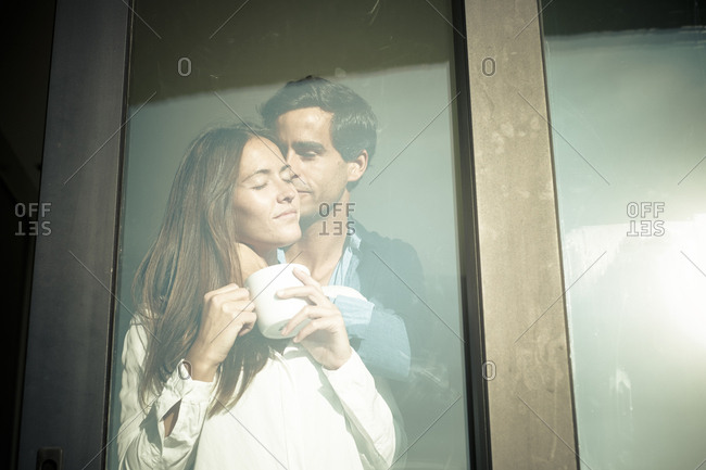 Young couple in love at the window