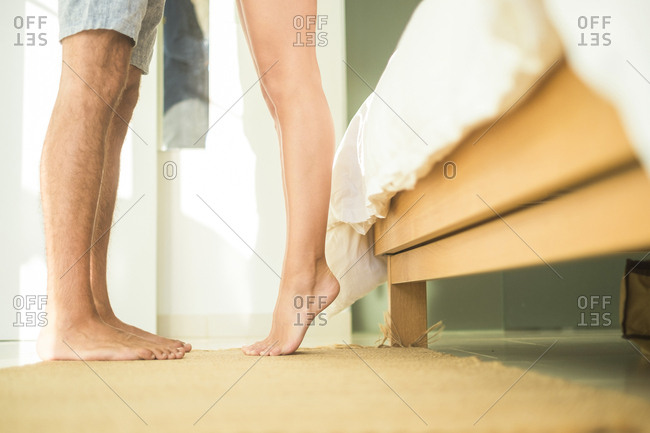 Low section of couple standing in bedroom
