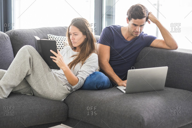 Young couple on couch relaxing with book and laptop