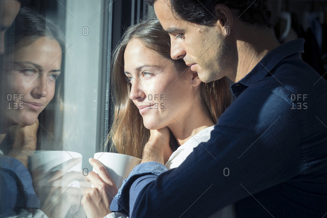 Smiling young couple looking out of window