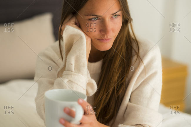 Young woman sitting on bed with cup of coffee