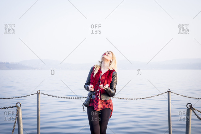 Blond woman standing in front of a lake listening music with smartphone and earphones looking up