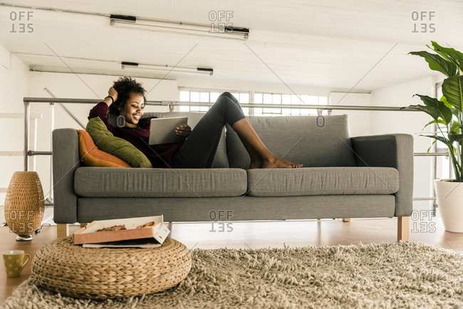 Smiling young woman lying on couch using tablet