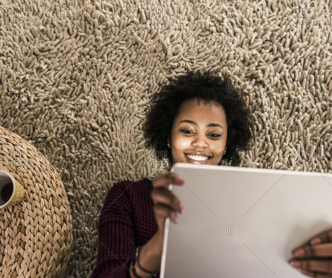 Smiling young woman lying on carpet using tablet