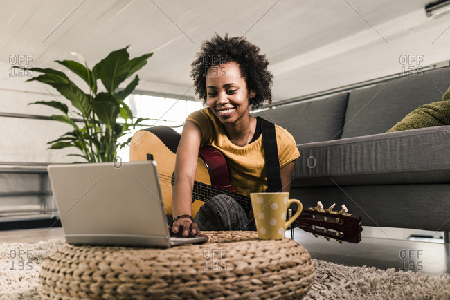 Smiling young woman at home with guitar and laptop