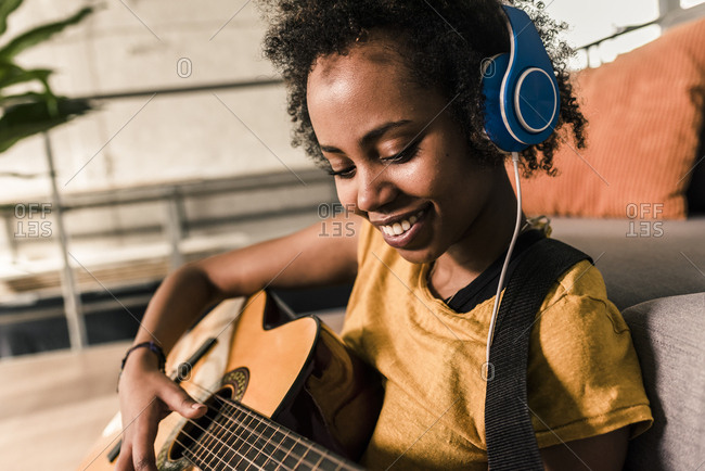 Smiling young woman at home with headphones playing guitar