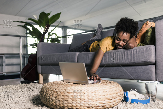 Smiling young woman lying on couch using laptop