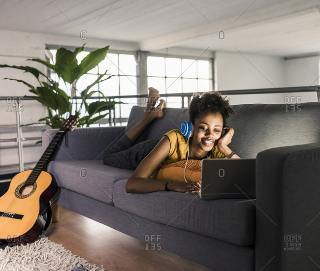 Smiling young woman with headphones lying on couch using laptop next to guitar