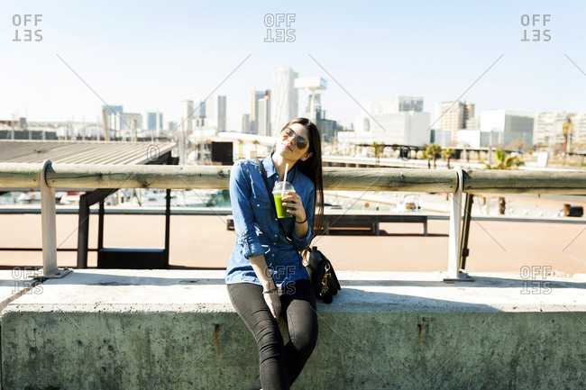 Spain- Barcelona- smiling young woman with beverage enjoying sunlight