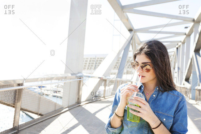 Spain- Barcelona- young woman with beverage on a bridge