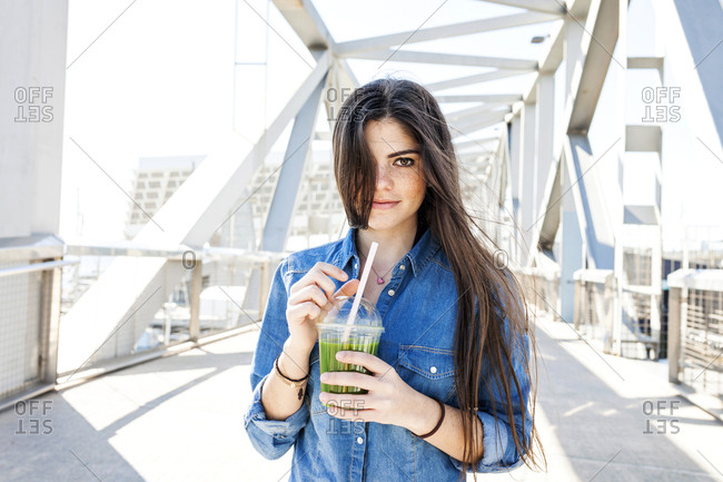 Spain- Barcelona- portrait of smiling young woman with beverage on a bridge