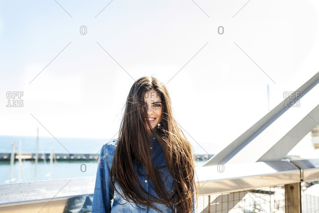 Smiling young woman with long brown hair standing on bridge