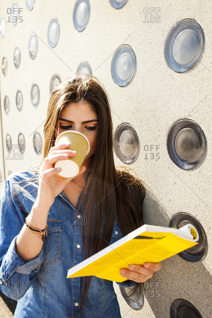 Young woman with coffee to go reading book