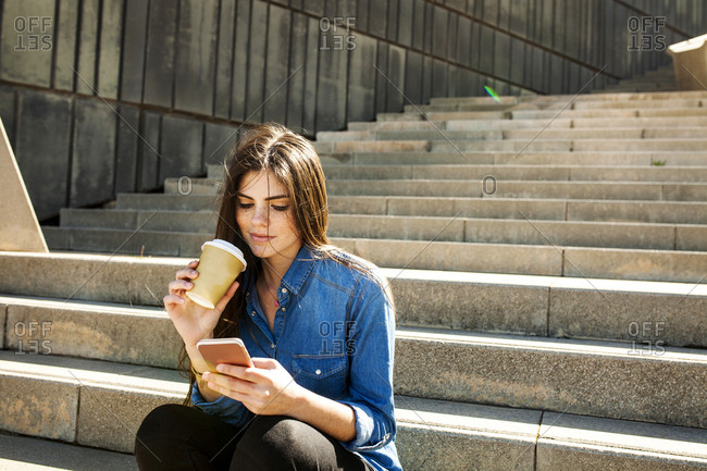 Young woman with coffee to go sitting on stairs looking at cell phone