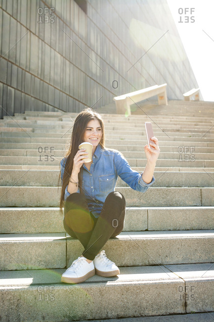 Young woman with coffee to go sitting on stairs taking selfie with smartphone