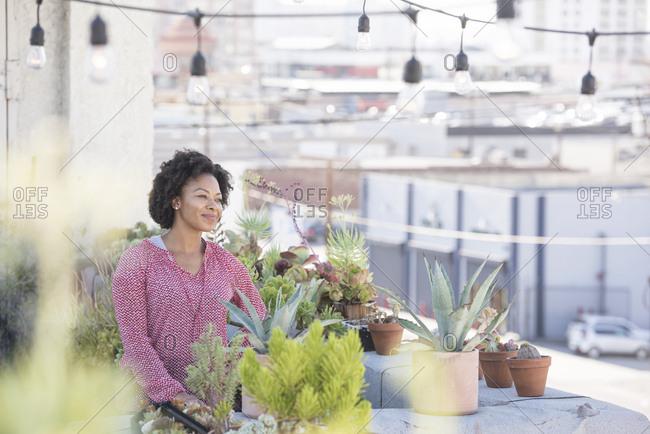 Smiling woman standing in her rooftop garden