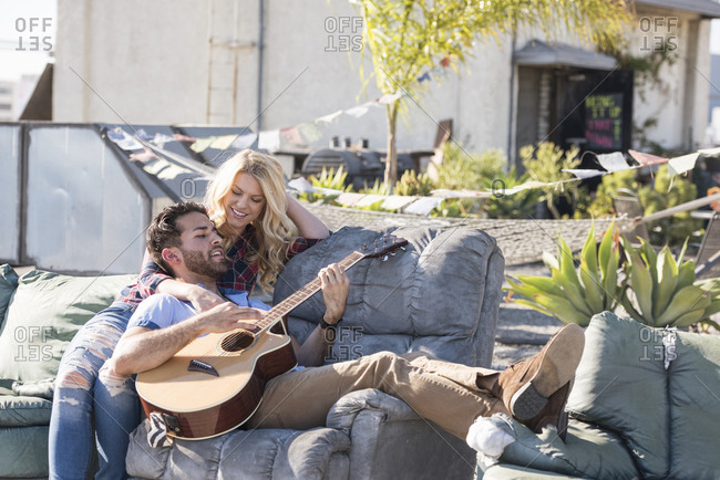 Couple on rooftop sitting on sofa and playing guitar