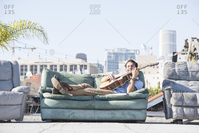 Young man on rooftop lying on sofa and playing guitar