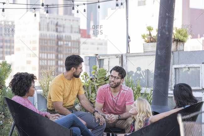Friends having a rooftop party- talking and chatting