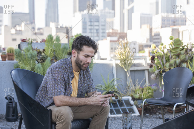 Young man sitting on rooftop terrace checking smart phone messages