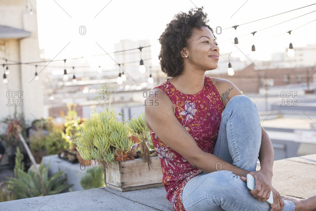 Young woman sitting on rooftop terrace- enjoying the sun