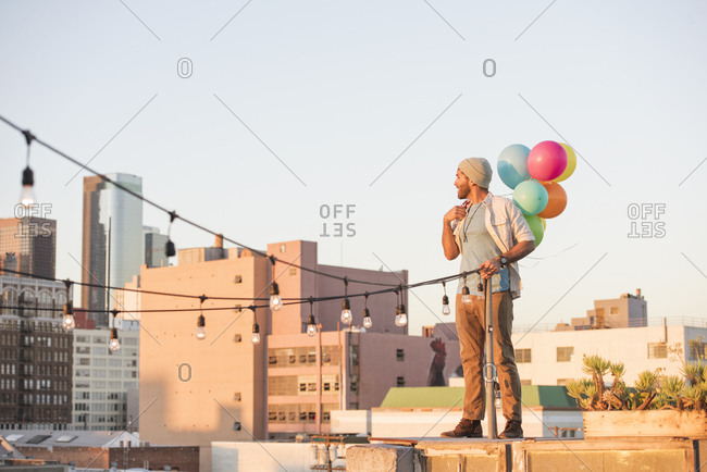 Young man standing on rooftop- holding balloons