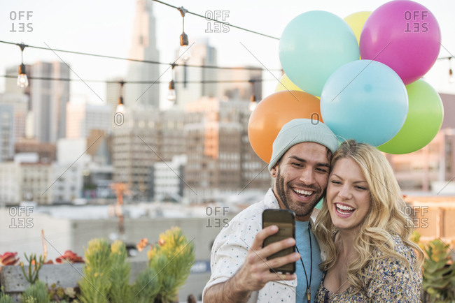 Young couple with balloons standing on rooftop terrace- using smart phone