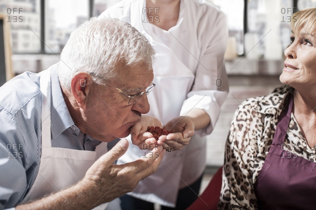 Senior man smelling seeds from chef's hand in cooking class