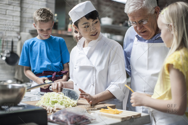 Female chef instructing kids in cooking class