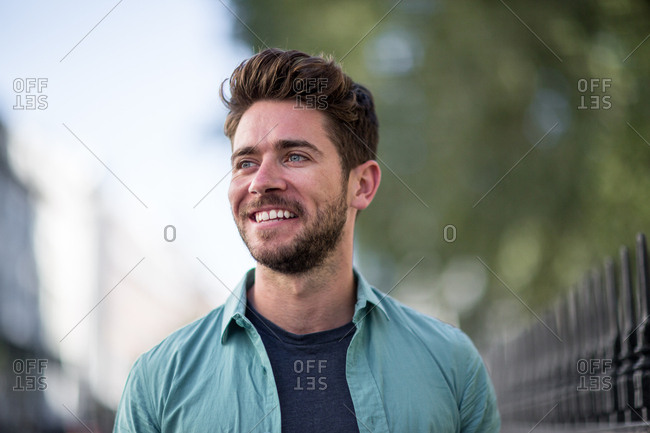 Young adult walking down street smiling