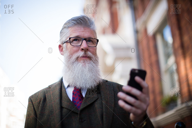 Senior male walking down street using smartphone